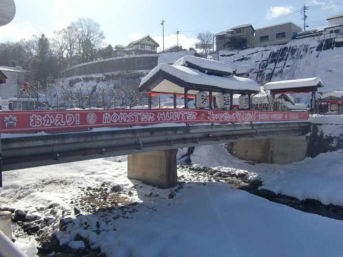 Puente cercano al pueblo de Shibu Onsen. Cartel colgado del evento de Monster Hunter